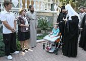 Святейший Патриарх Кирилл благословил девочку, страдающую детским церебральным параличом, и подарил ей специальную коляску для детей с ограниченными возможностями