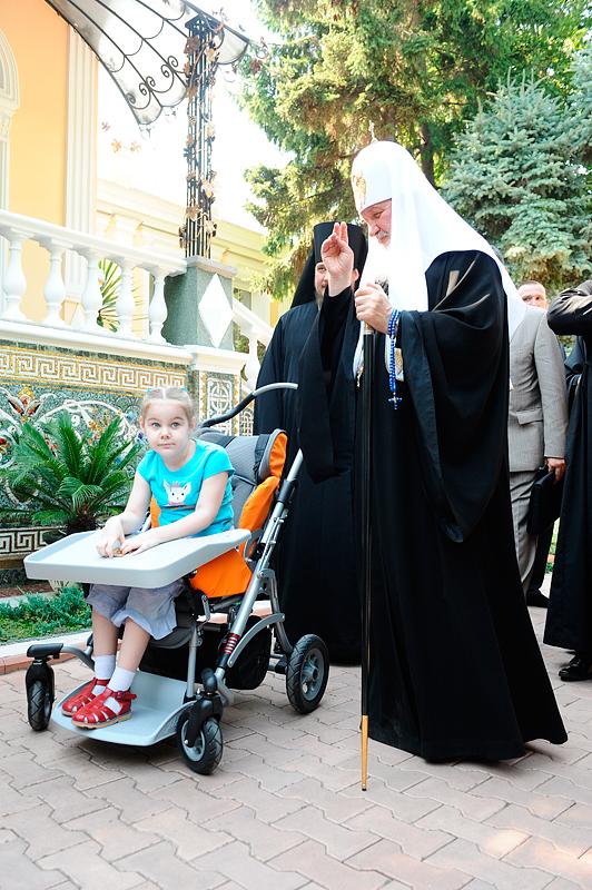 Вручение подарка ребенку с ограниченными возможностями во время визита на Украину